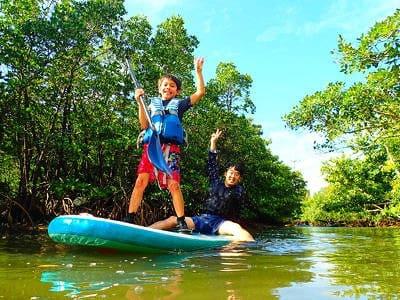 西表島のクーラ川でSUPを楽しむ少年