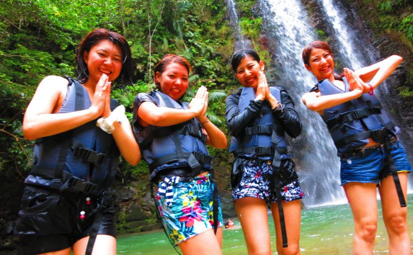 沖縄の名護でリバートレッキングツアーで滝をバックに記念撮影