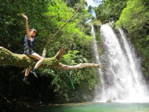 沖縄の滝近くで木に登る女性