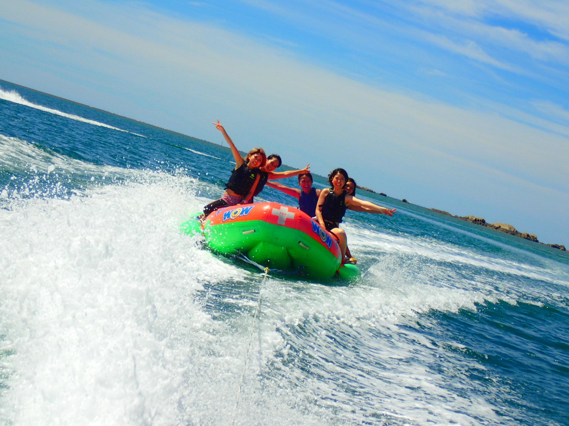 沖縄の宜野座村の海でバナナボートに乗るグループ