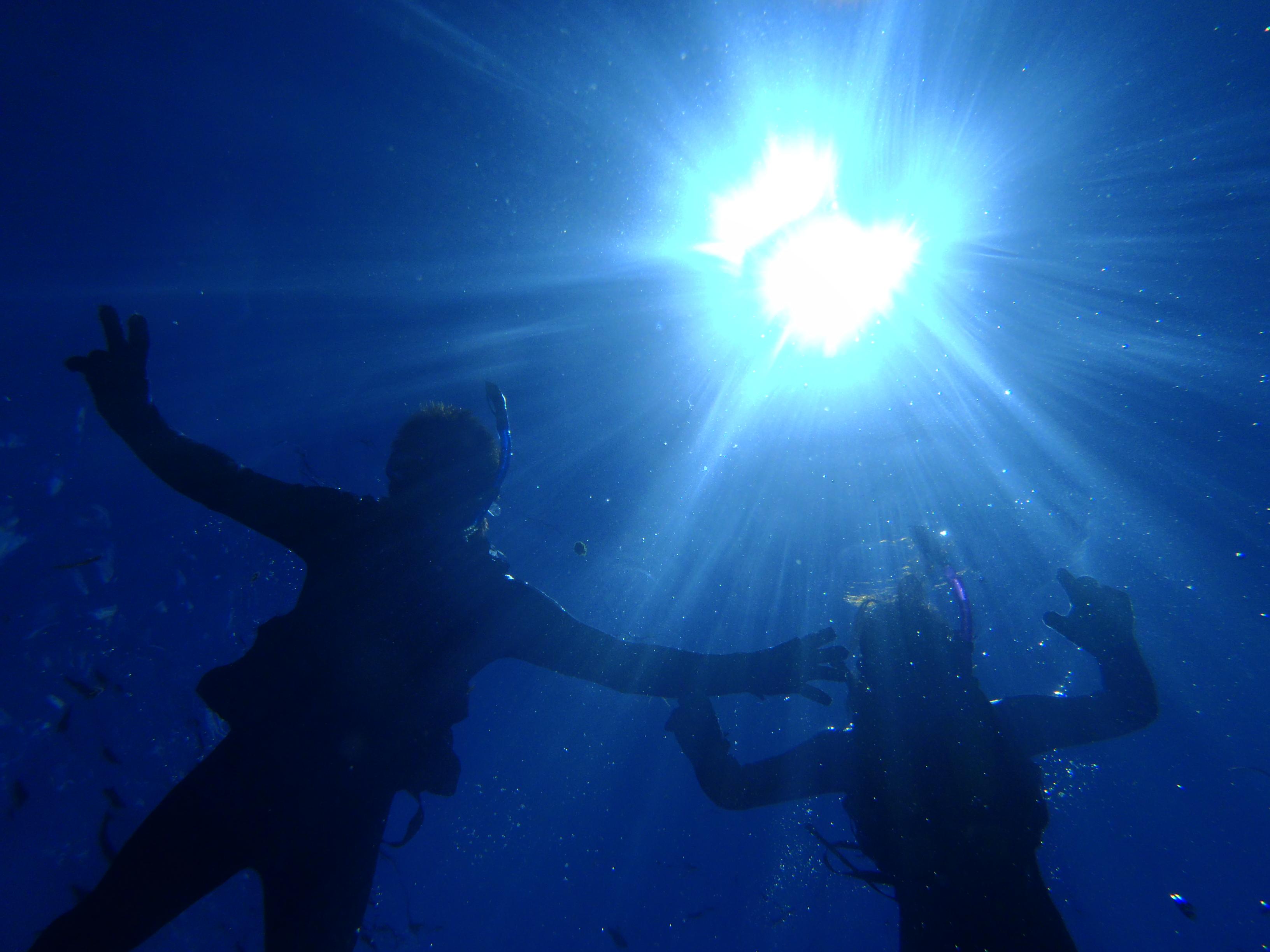 沖縄の青の洞窟で透き通った海の中をシュノーケリング