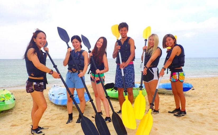 沖縄の浜辺でシーカヤックツアーに参加しようとするグループ