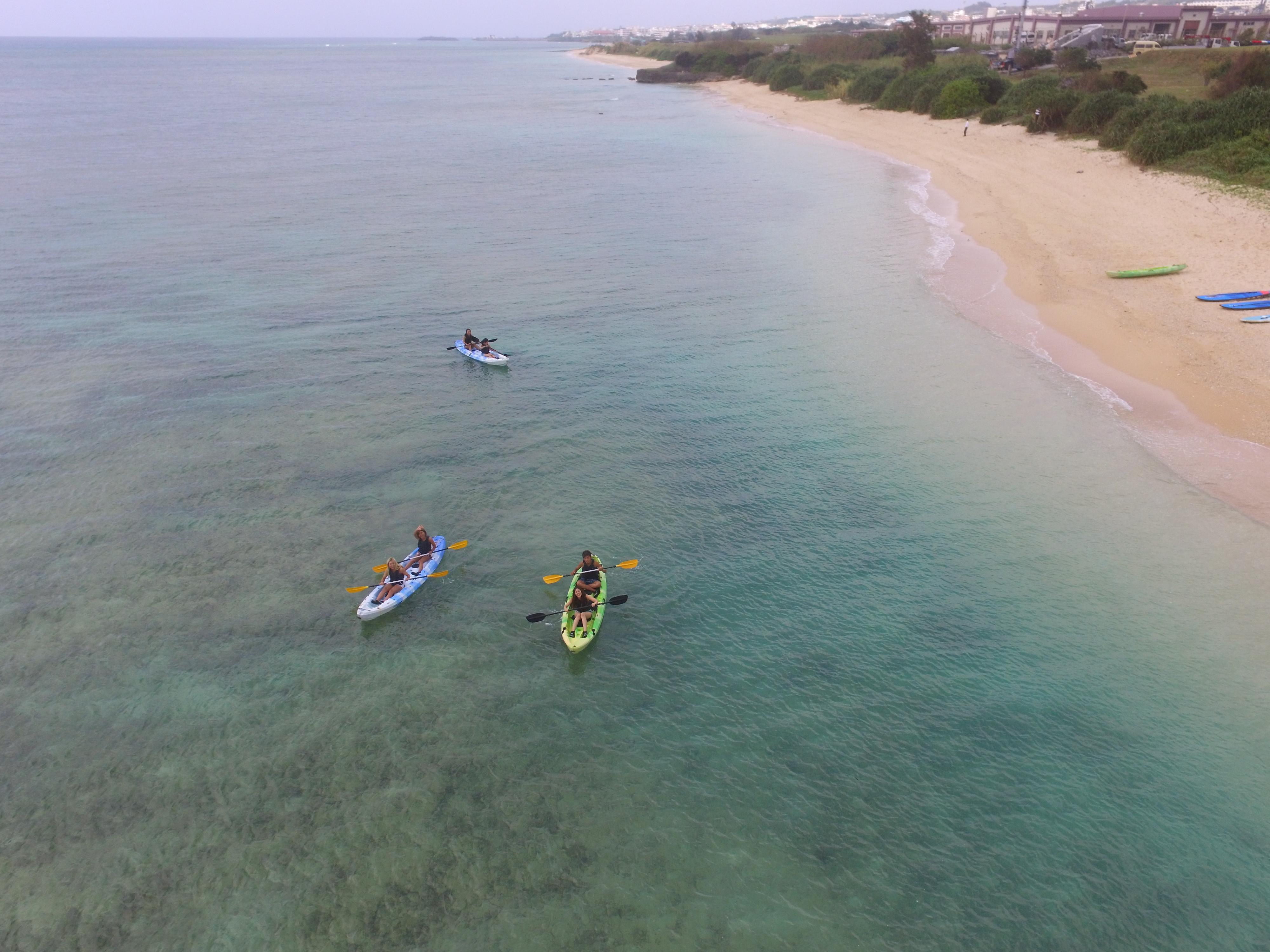 沖縄の読谷村の海でシーカヤックをするグループ