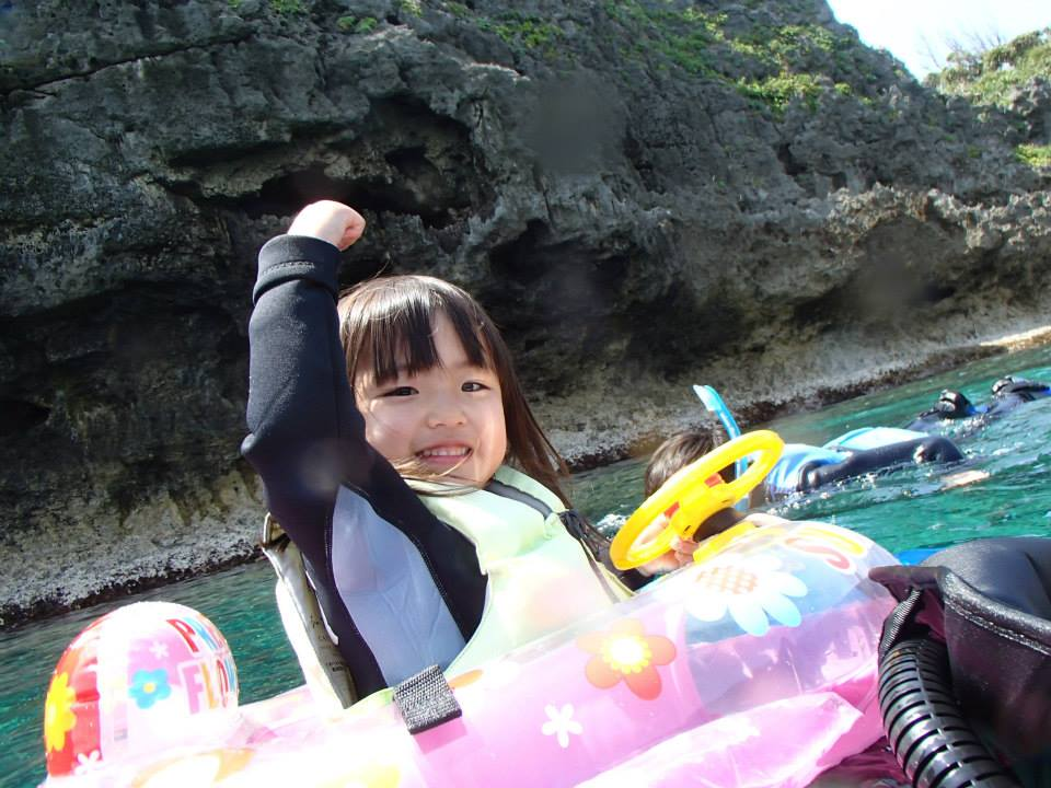 沖縄の青の洞窟で浮き輪で泳ぐ子ども