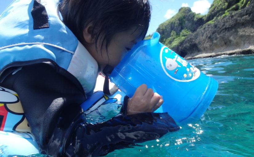 沖縄の青の洞窟で海の中をのぞく子ども