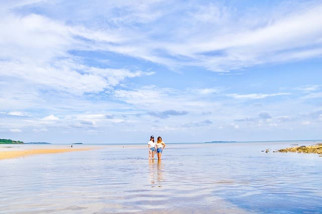 朝の海でポーズする女性
