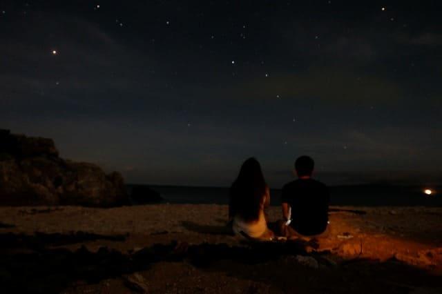 ビーチで宮古島の星空を眺めるカップル