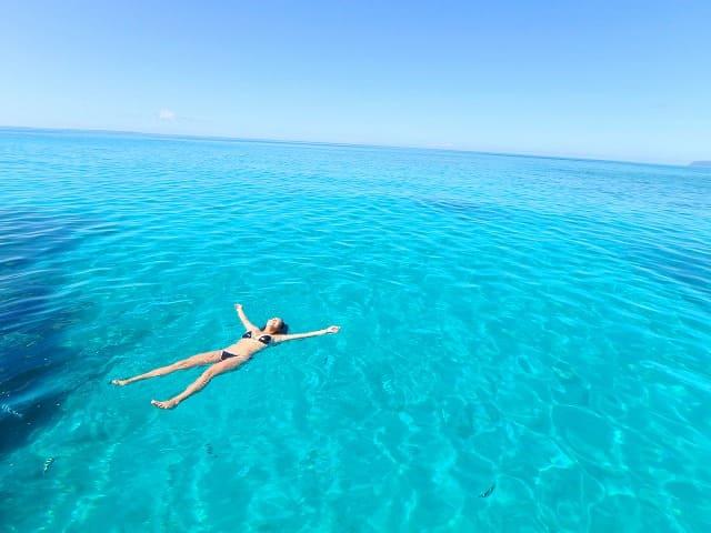 真っ青な海に浮かぶ女性