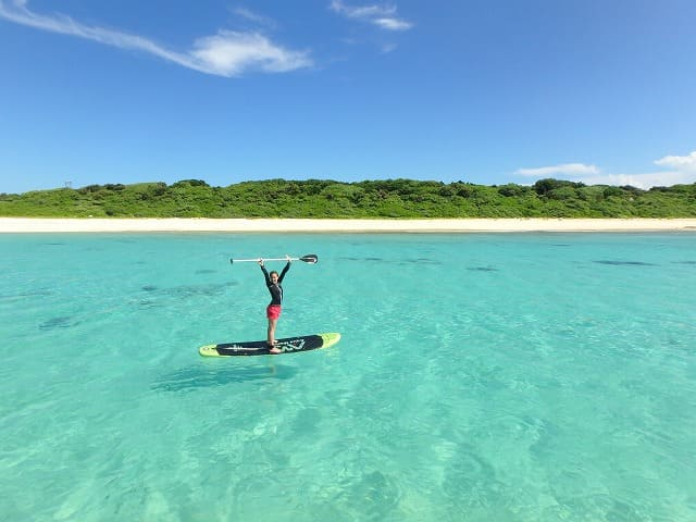 綺麗な海でSUPを楽しむ女性
