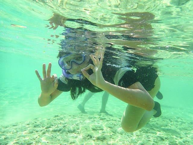 透明度抜群の西表島の海でシュノーケリングをする女性