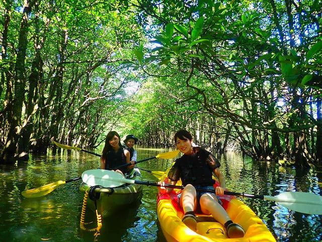 西表島のクーラ川でカヌーをする女性