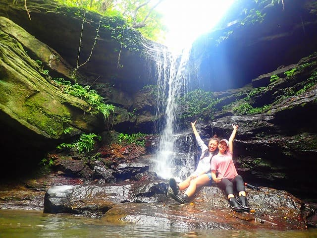 クーラの滝前でポーズをとる参加者