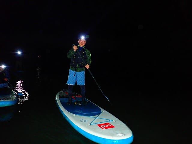 夜のマングローブSUPクルーズする男性