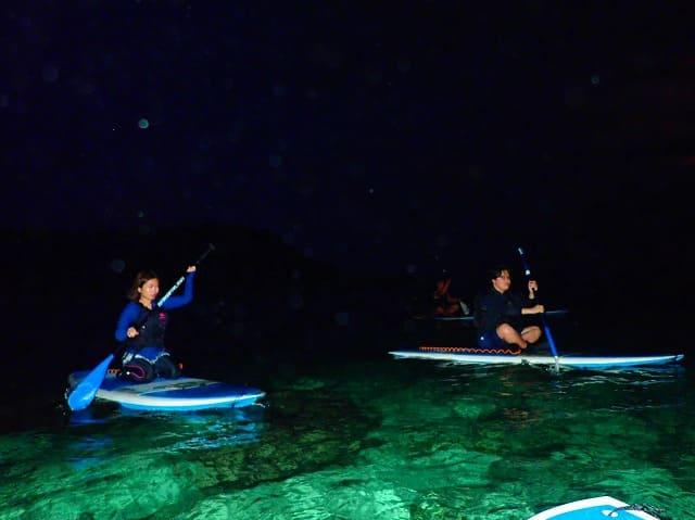 夜の宮古島SUPクルージングをする女性