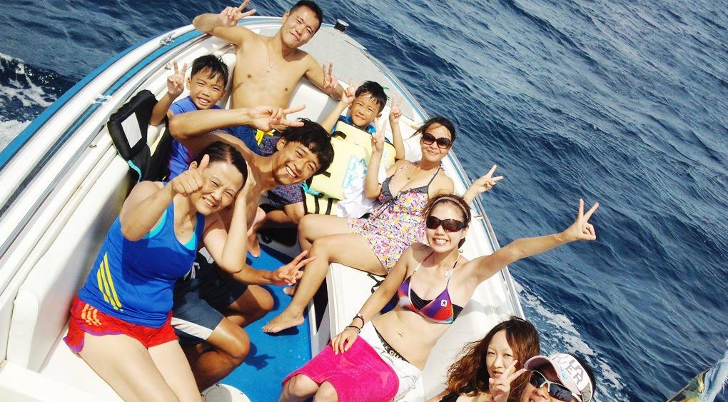 沖縄の海でパラセーリングをしに船に乗るグループ