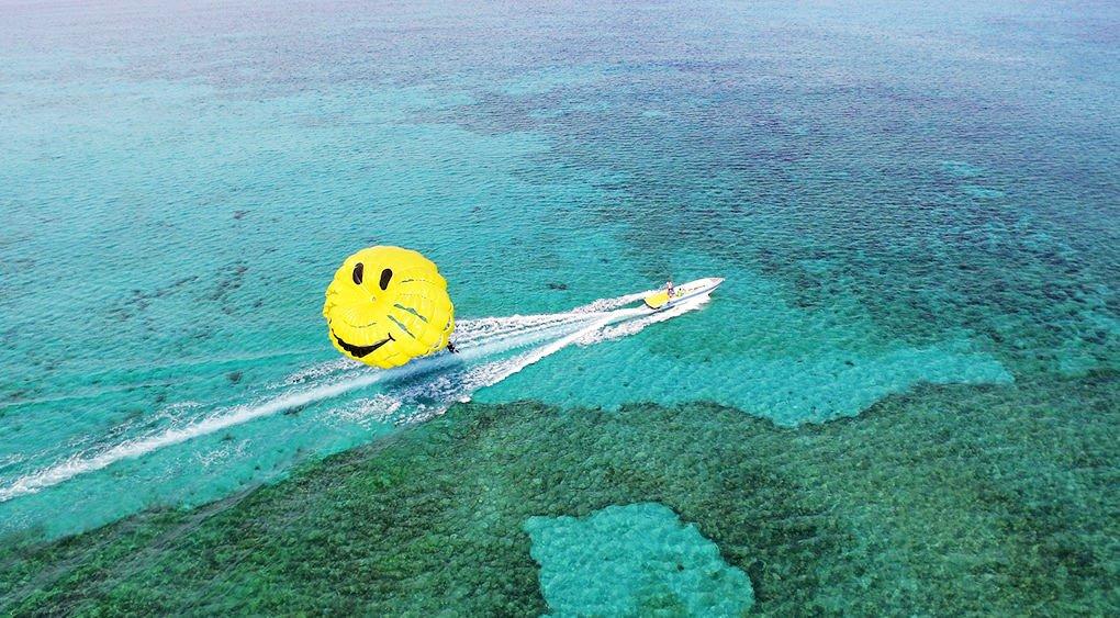 沖縄の青い海ににこちゃんパラセーリングが映える