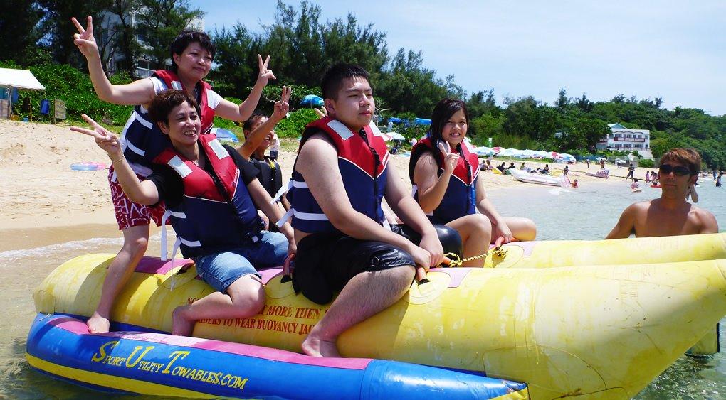 沖縄のうるま市でバナナボートに乗るグループ