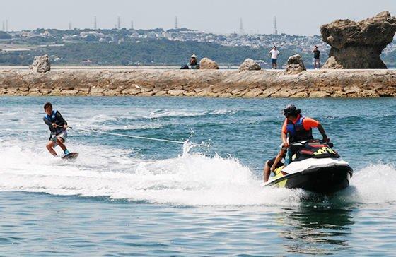 沖縄のうるま市の海でウエイクボードをする男の子