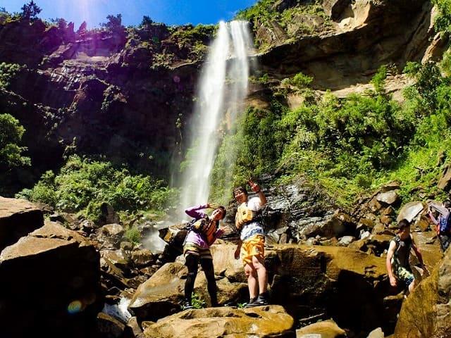 滝つぼの前でポーズする女性