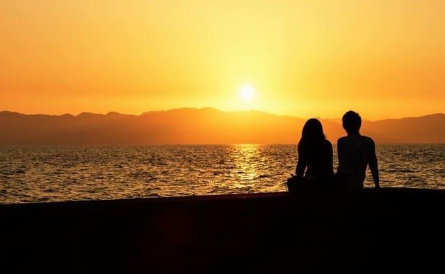 カップルで夕日を見る