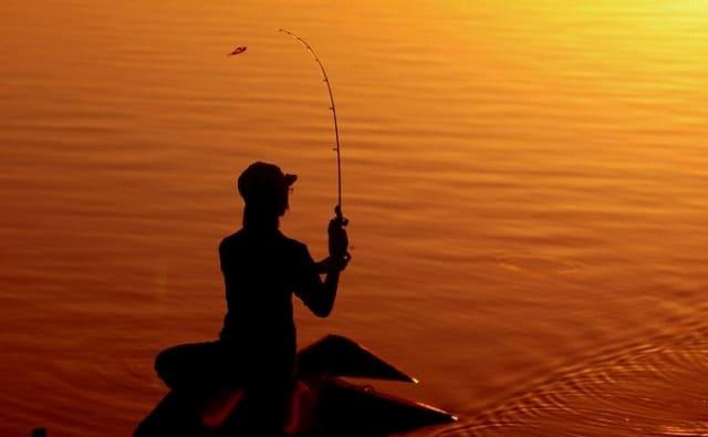 夕日の中で釣りをする女性