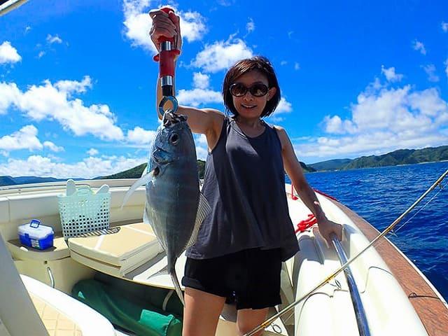 釣った魚と写真を撮る女性
