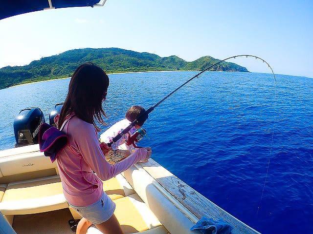 女性が魚を釣り上げる