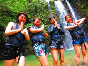 ター滝の前でポーズをとる女性たち