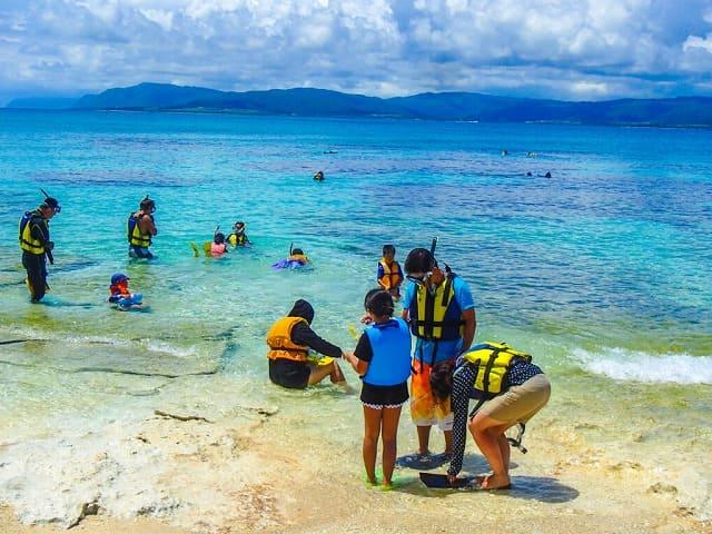 西表島のビーチでシュノーケリングをする人たち
