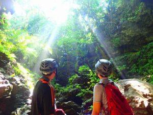 ジャングルの奥地にある鍾乳洞前で休憩するカップル
