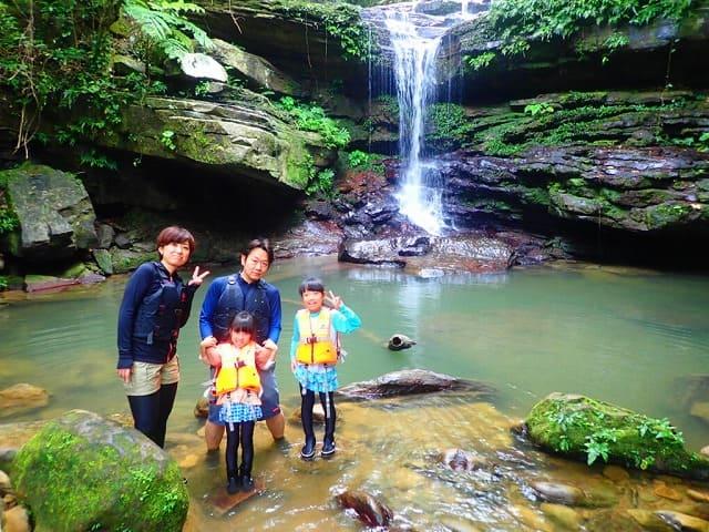 西表島のクーラの滝で記念撮影する家族