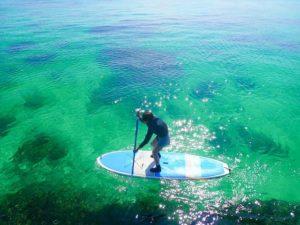 小浜島の透明な海でSUPをする女性