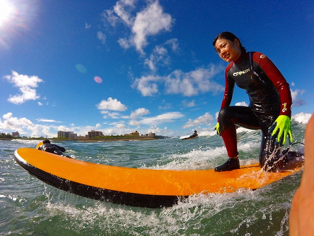 沖縄の海でサーフィンをする女性